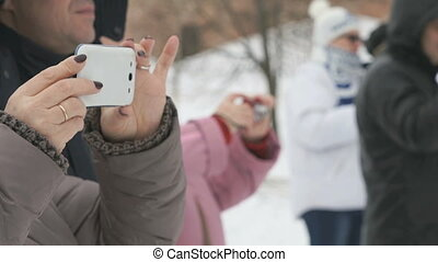 Woman takes sports on a white phone in winter