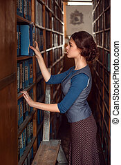 Woman taking a book from bookshelf.