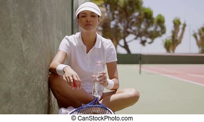 Woman taking a break from tennis to drink water
