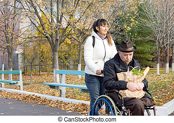 Woman taking a disabled man grocery shopping