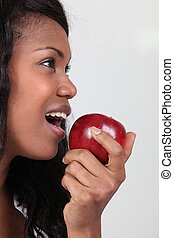 Woman taking a large bite out of a red apple