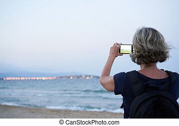Woman taking a photo of a sea on smart phone on sunset