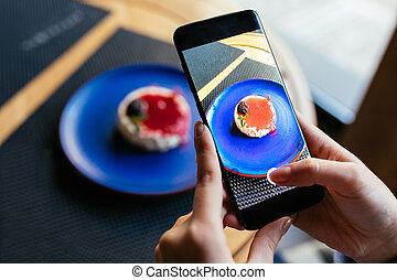 Woman taking a photo of delicious cake
