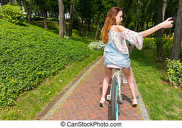 Woman taking a photo while sitting on her bike