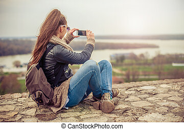 Woman taking a photo with cell phone