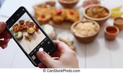 Woman taking a photo with smartphone of deep fried Crispy ...