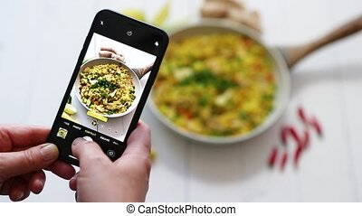 Woman taking a photos with mobile phone of delicious fried ...
