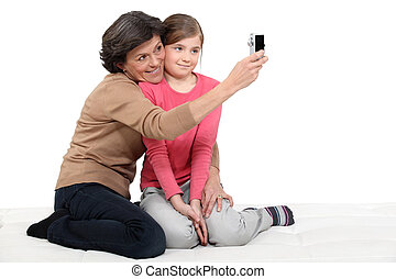 Woman taking a picture of herself with her granddaughter