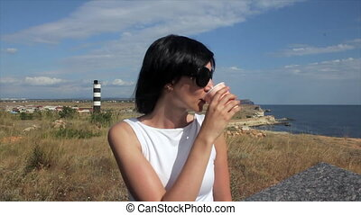Woman Taking a Sip of Coffee by Sea in the background lighthouse