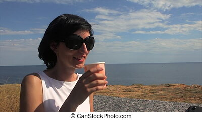 Woman Taking a Sip of Coffee by Sea in the background