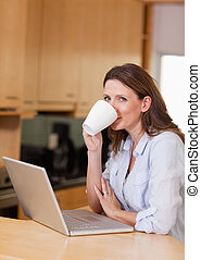 Woman taking a sip of coffee next to laptop