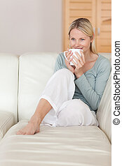 Woman taking a sip of coffee on the sofa