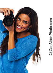 Woman taking a snap, smile please - Young woman photographer...