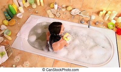 Woman taking bath and wash sholder on foam in her bathroom....