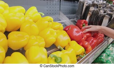 Woman taking red bell pepper in a grocery store.