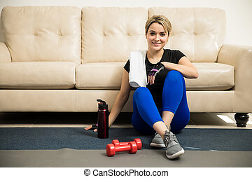 Woman taking break from exercising at home