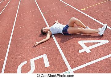 Woman taking break on track field