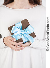 woman taking brown and blue gift