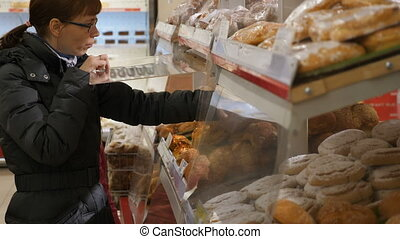 Woman taking buns at grocery store