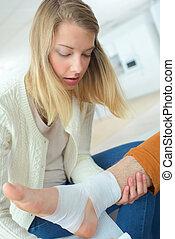 woman taking care of boyfriends ankle