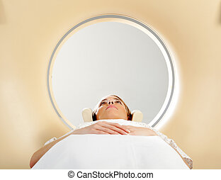 Woman taking CT Scan - A woman laying down with eyes open...