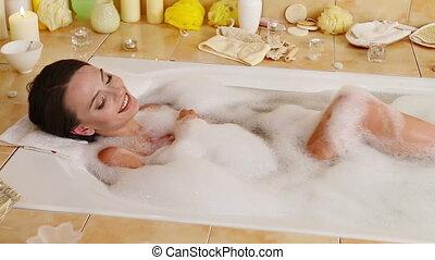 Woman taking  foam bath  and wash legs in her bathroom. Dolly system.