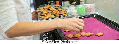 Woman taking freshly baked home made cookies from the tray