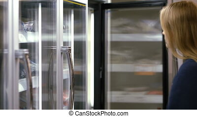 Woman taking frozen product from the fridge in the shop