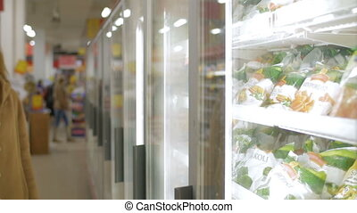 Woman taking frozen product in the shop fridge