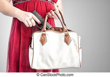 Woman taking gun from purse