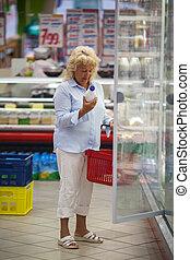 Woman taking milk from the fridge in supermarket