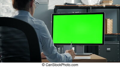 Back view of business woman taking notes during video conference on modern computer with chroma key screen. Online meeting and conversation. Concept of technology.