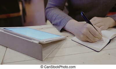 Woman taking notes in notebook, touch pad nearby - Close-up...