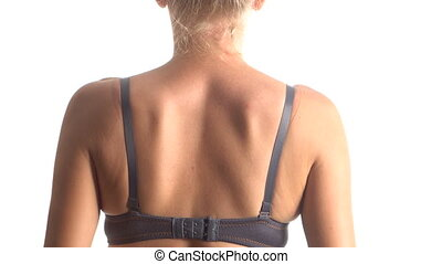 Woman taking off her bra - Back view of woman taking off her...