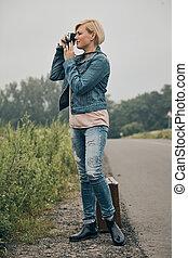 Woman taking photo in a field of Flowers