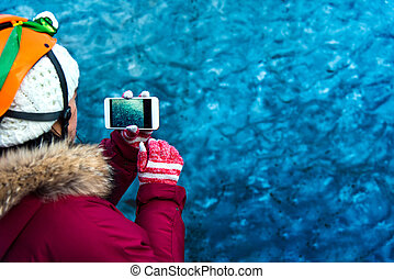 Woman taking photo in blue ice cave in Iceland