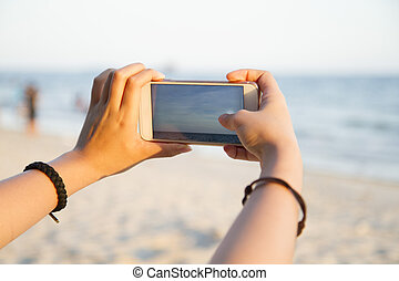 Woman taking photo of beach landscape with smart phone