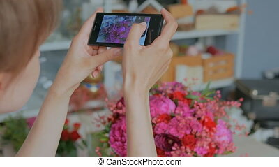 Woman taking photo of beautiful bouquet with smartphone. -...