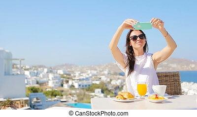 Woman taking photo of breakfast using mobile smart phone.