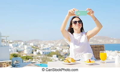 Woman taking photo of breakfast using mobile smart phone. Girl taking pictures of food on luxury travel vacation for social media. Beautiful female in resort in Mykonos, Greece, Europe.