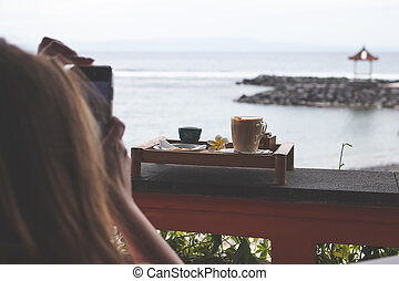Woman taking photo of coffee outdoors in the restaurant. Bali island.