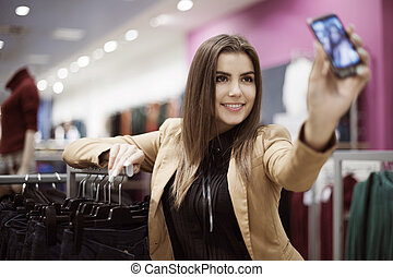 Woman taking photo of herself in shopping mall