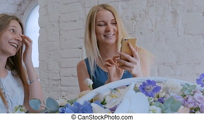 Woman taking photo of large floral basket with flowers with smartphone.