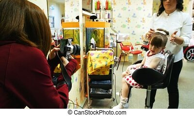 Woman taking photo of little girl on camera