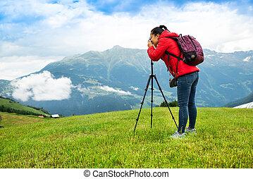 Woman Taking Photo Of Mountain Landscape