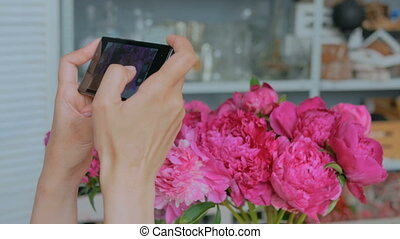 Woman taking photo of pink peonies with smartphone.