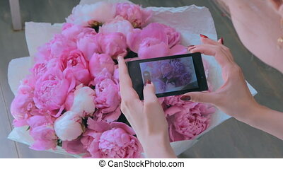 Woman taking photo of pink peonies with smartphone. -...