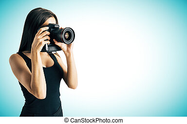 Woman taking photo on blue background