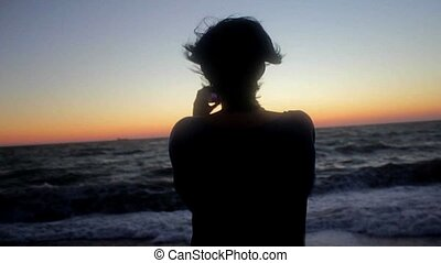 Woman taking photo on the beach. Handheld shot