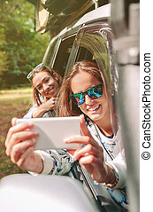 Woman taking photo to her friend through the window car